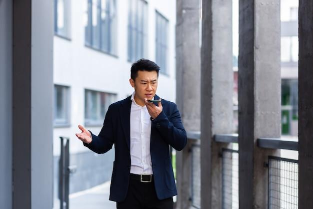 怒って真面目な成功したアジアのビジネスマンは、電話を使用して従業員に情報を説明し、外のオフィスの近くで話します
