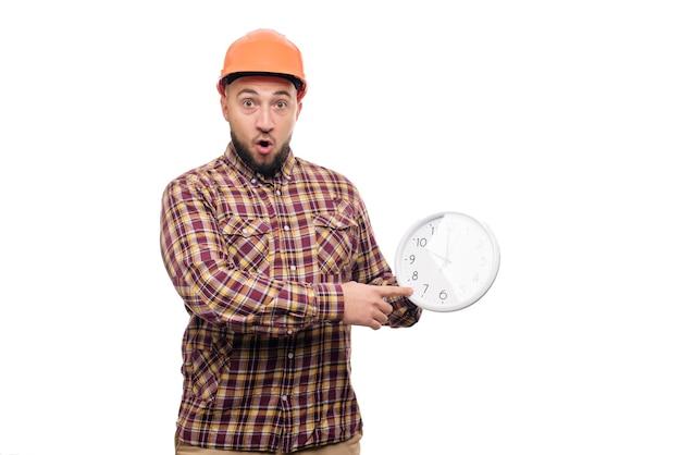 白い背景で隔離の大きな目覚まし時計を手に持っている保護構造のオレンジ色のヘルメットの怒りとショックを受けたビルダーの労働者。働く時間。建物の建設時間。