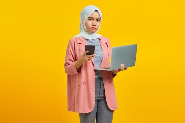 파란색 배경에 휴대전화와 노트북을 들고 있는 화나고 불행한 젊은 아시아 여성