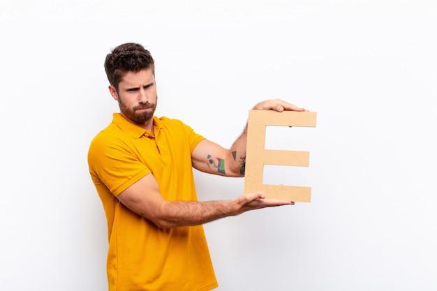 Злой, гнев, несогласие, держа букву е алфавита, чтобы сформировать слово или предложение.