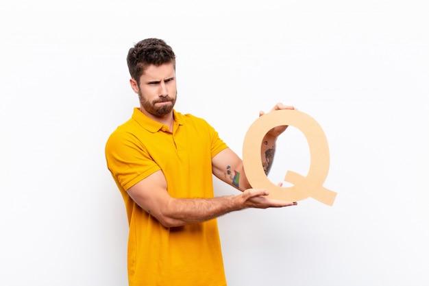 Злой, гнев, несогласие, держа букву q в алфавите, чтобы сформировать слово или предложение.