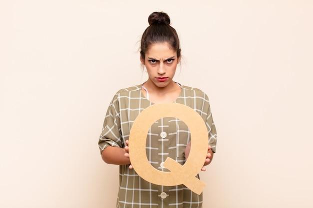 Злой, гнев, несогласие, держа букву q алфавита, чтобы сформировать слово или предложение.