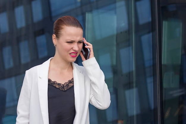 Angry, annoyed, irritated businesswoman talking, screaming, swearing on cell phone outdoor. female boss yells, shouting at employee on smartphone. unpleasant conversation, bad connection, hard to hear