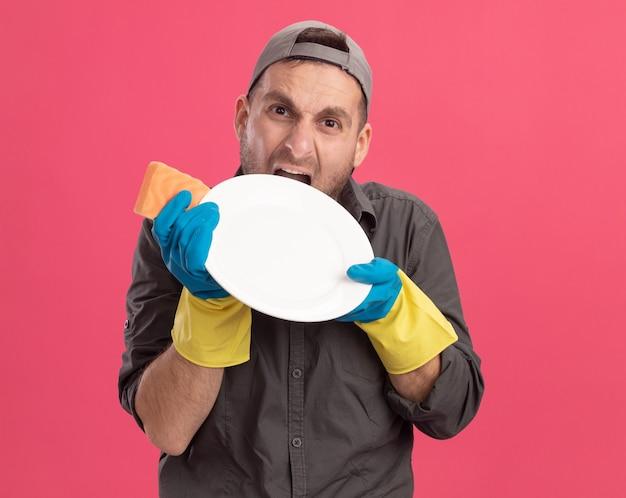 Arrabbiato e infastidito giovane uomo delle pulizie che indossa abiti casual e berretto in guanti di gomma tenendo la piastra e la spugna andando selvaggio mordere la piastra in piedi sopra il muro rosa