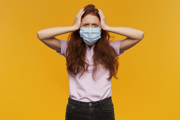 Angry annoyed young woman wearing medical protective mask keeps hands on head and looks irritated isolated over yellow wall