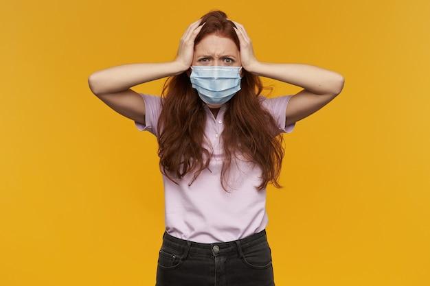 医療用保護マスクを身に着けている怒っているイライラした若い女性は頭に手を保ち、黄色の壁の上に孤立してイライラしているように見えます