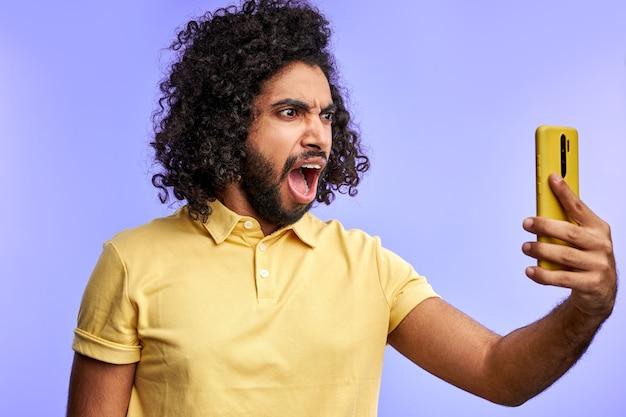 携帯電話でオンラインで話している間、スマートフォンで叫んでいる怒っているアラビア語の男性、悲鳴を上げる、紫色の空間に孤立