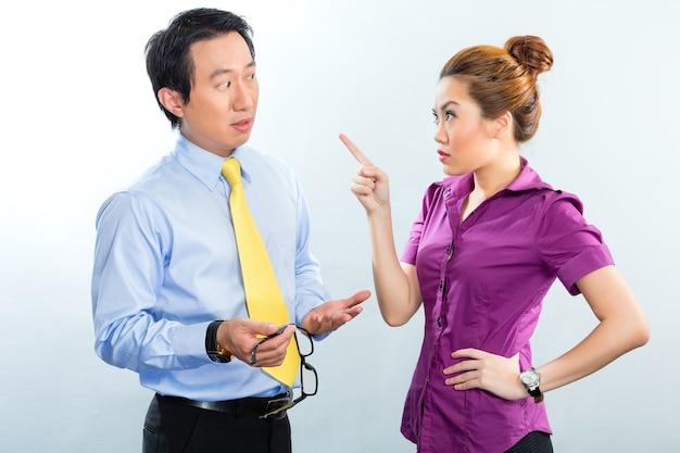 Гневный спор между коллегами в азиатском бизнес-офисе
