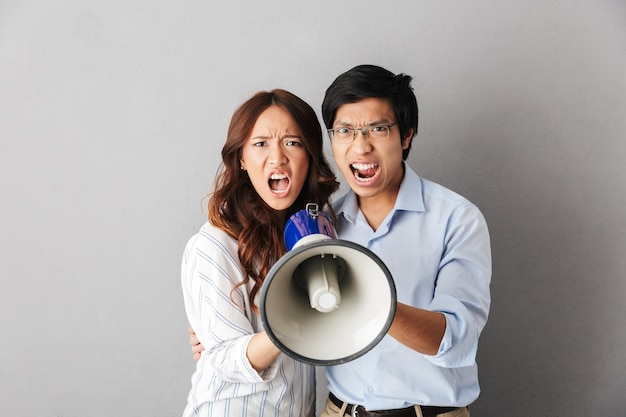 Angry asian business couple standing isolated, holding loudspeaker