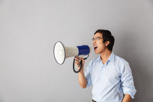 Angry asian business man standing isolated, screaming at a loudspeaker