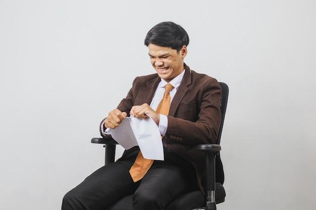 スーツとネクタイの怒っているアジアのビジネスマンは、紙を引き裂く間、オフィスの椅子に座っています。