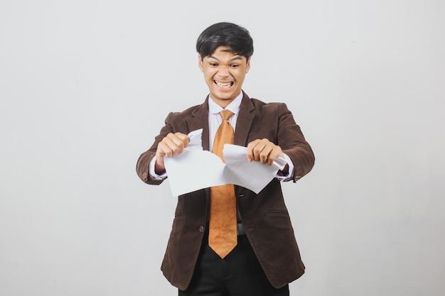 スーツとネクタイで怒っているアジアのビジネスマンが動揺して紙を引き裂く