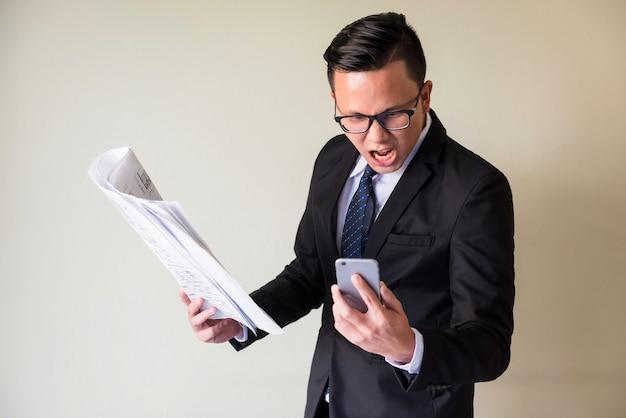 안경, 양복, 넥타이를 매고 화난 아시아 사업가가 종이 청사진과 화상 통화를 하고 전화나 스마트폰으로 소리를 지르며 건설 계획 지연에 대해 팀원들에게 불평합니다. 공격적인 보스.
