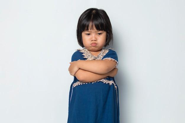 白い背景で隔離の腕を組んで怒っているアジアの少女