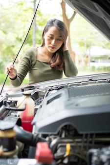 怒っているアジアの女性と路上で車が故障した後、助けを求めて携帯電話を使用しています。車両エンジンの問題または事故の概念と専門の整備士による緊急援助