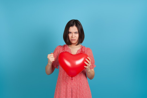 Angry asian woman holding  red heart  balloon and clenching  hand into  fist