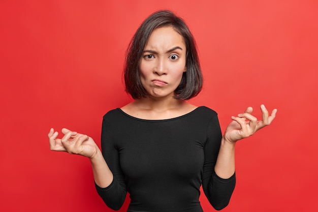 Angry asian woman raises eyebrows from annoynace keeps palms sideways shrugs shoulders with hesitation wears black jumper isolated over vivid red wall looks with bewilderment.