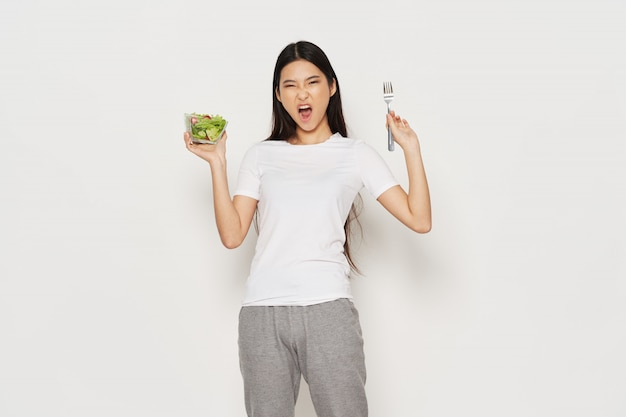 Angry asian woman with salad