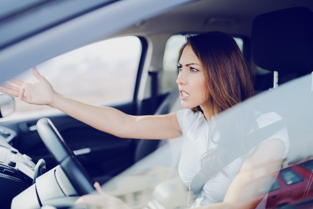 Angry attractive caucasian brunette yelling at other drivers while sitting in car.