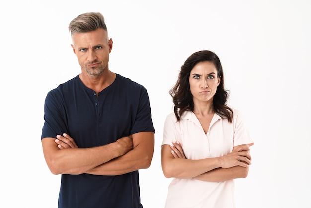 白い壁の上に孤立して立っているカジュアルな服を着て、腕を組んで怒っている魅力的なカップル