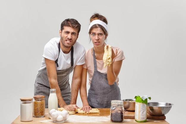 怒っているパン屋は生地をこね、何か間違ったことをし、レシピに従わず、自家製ピザを準備し、小麦粉で汚れて立ち、白い壁に隔離され、必要な食品に囲まれています