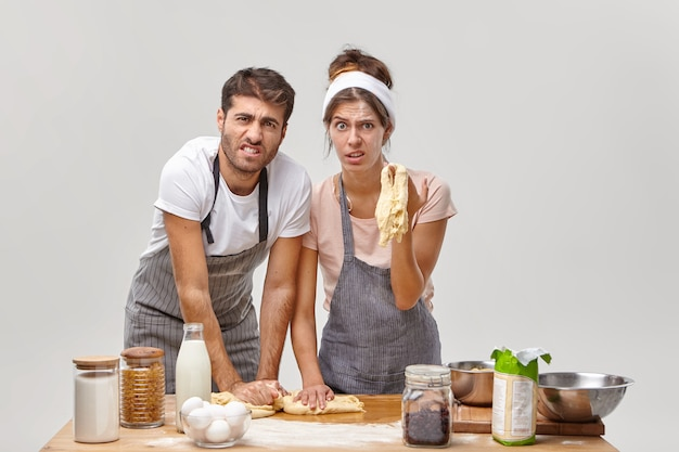 Angry bakers knead dough together, did something wrong, didnot follow recipe, prepare homemade pizza, stand dirty with flour, isolated on white wall, surrounded with necessary food products