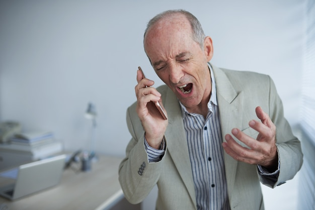 Angry bald caucasian businessman holding mobile phone and screaming with rage