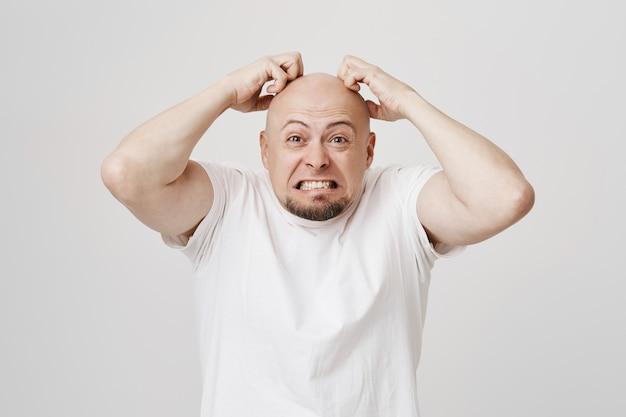 Злой лысый парень сжимает зубы и почесывает голову