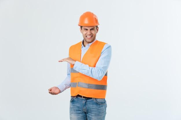 横に手を握って何かを説明している怒っているひげエンジニア、白い背景で隔離の黄色いベストとオレンジ色のヘルメットとカロシャツとジーンズを着ている男。