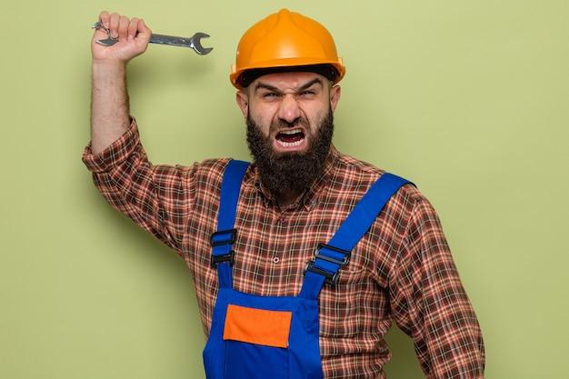 緑の背景の上に立っている攻撃的な表情で叫んでいるカメラを見て建設制服と安全ヘルメットスイングレンチで怒っているひげを生やしたビルダーの男
