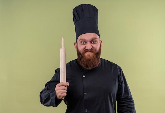 Un uomo arrabbiato chef barbuto in uniforme nera che tiene il mattarello mentre guarda su una parete verde