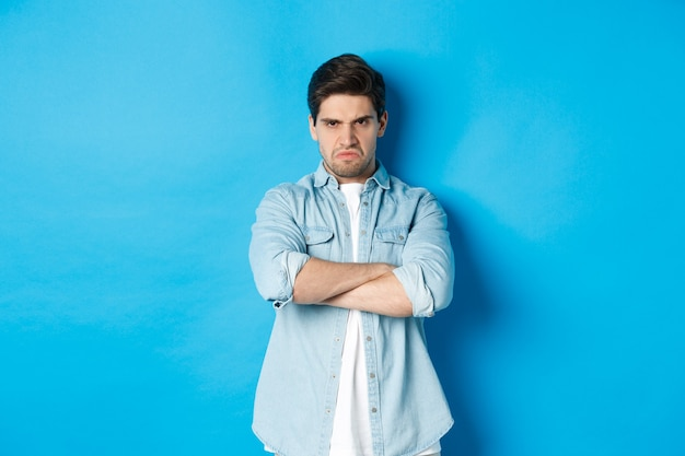 Angry bearded guy crossing arms on chest, frowning, looking mad and offended, standing against blue background