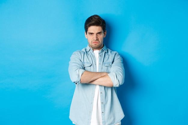 怒っているひげを生やした男が胸に腕を組んで、眉をひそめ、怒って気分を害し、青い背景に立っている