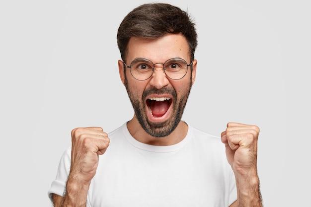 Злой бородатый парень с безумным выражением лица, от гнева поднимает брови, громко кричит, носит обычную белую футболку, выражает раздражение, чувствует себя сумасшедшим, изолированным от стены. пожалуйста, не шумите!