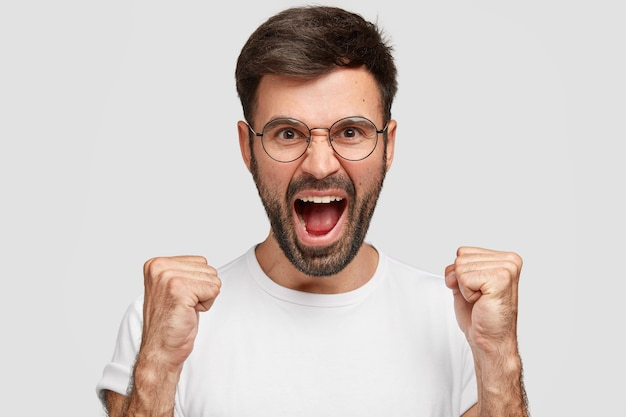 Angry bearded guy with mad expression, raises eyebrows with anger, scream sloudly, wears casual white t-shirt, expresses annoyance, feels crazy, isolated over wall. don`t make noise, please!
