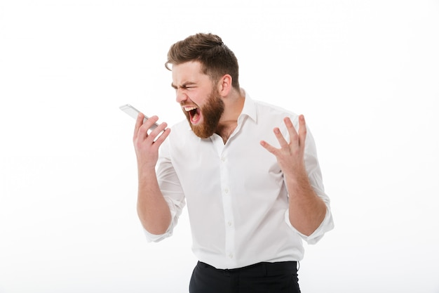 Angry bearded man in business clothes screaming at smartphone