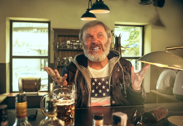 パブでアルコールを飲み、テレビでスポーツ番組を見ている怒っているひげを生やした男。私の好きなティームとビールを楽しんでいます。テーブルに座っているビールのマグカップを持つ男。サッカーやスポーツのファン。人間の感情の概念