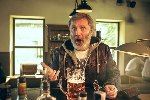 Uomo barbuto arrabbiato che beve alcolici nel pub e guarda un programma sportivo in tv. gustando il mio brulicare e la mia birra preferiti. uomo con boccale di birra seduto a tavola. appassionato di calcio o di sport. concetto di emozioni umane