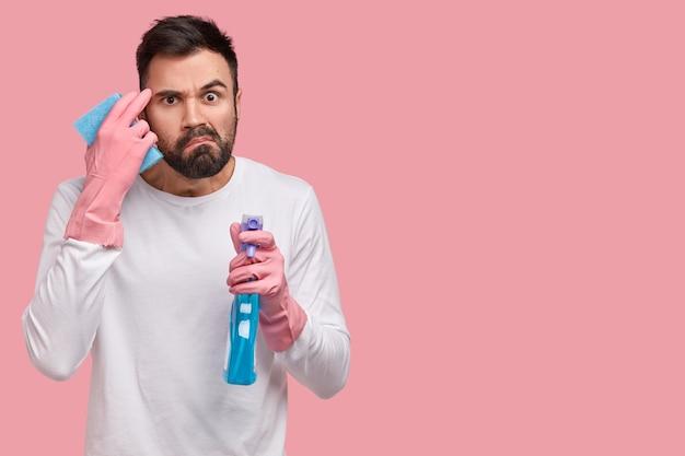 화난 수염 난 남자는 불만에 얼굴을 찌푸리고, 많은 일을하고, 방을 청소하고, 한 손에는 세제를 들고, 다른 손에는 걸레를 들고 있습니다.