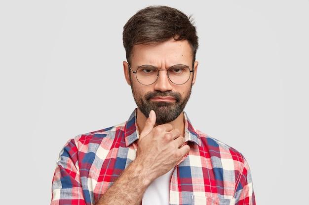 Злой бородатый мужчина угрюмо смотрит под брови, недоволен плохими новостями.