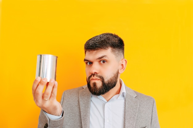 Angry bearded man holds oil barrel. a man holds metal can with provisions.