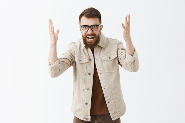 Злой бородатый мужчина в очках позирует у белой стены