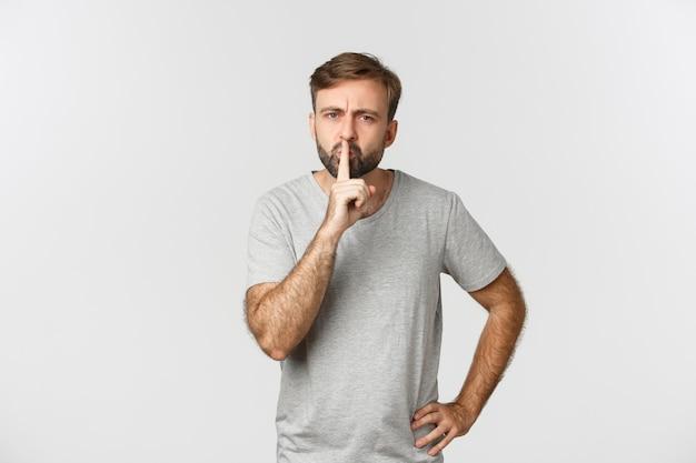 Злой бородатый мужчина в серой футболке, замолчал и нахмурился