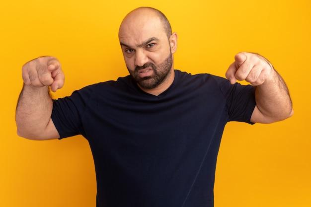 オレンジ色の壁の上に立っている人差し指で指している海軍のtシャツの怒っているひげを生やした男