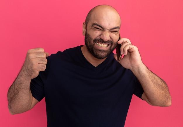 Uomo barbuto arrabbiato in maglietta blu scuro che sembra infastidito mentre parla al telefono cellulare pugno di serraggio in piedi sopra il muro rosa