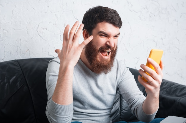 Angry bearded man screaming at smartphone while sitting on sofa in office