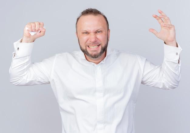 Uomo barbuto arrabbiato che indossa una camicia bianca che si scatena alzando le mani in piedi sul muro bianco