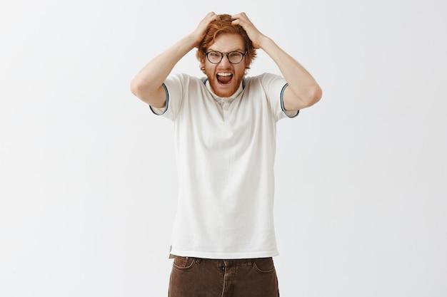 Ragazzo arrabbiato con la barba rossa in posa contro il muro bianco con gli occhiali