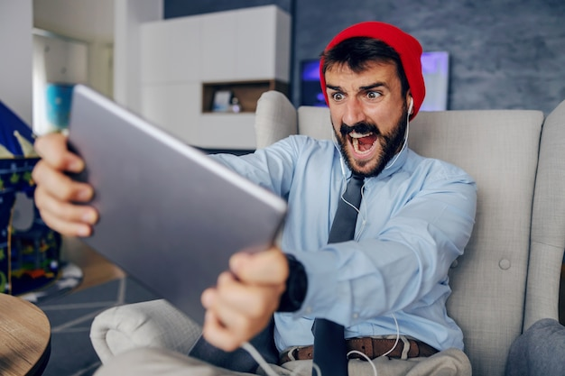 Angry bearded working dad dressed business casual sitting in chair at home and using tablet.