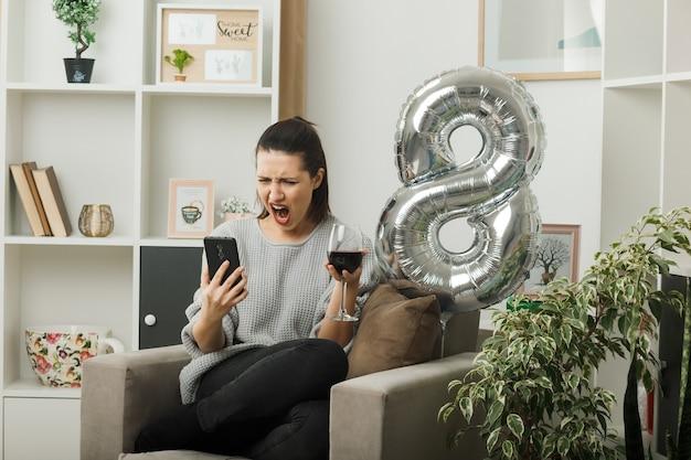 La bella ragazza arrabbiata durante la giornata delle donne felici con in mano un bicchiere di vino si fa un selfie seduto sulla poltrona in soggiorno